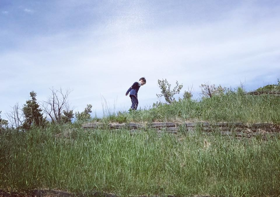 A child walks along a grassy hill, against a blue sky.